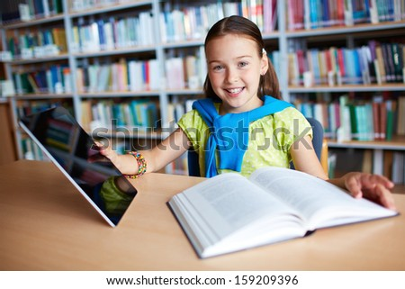 Portrait of a lovely girl with touchpad and open book sitting in library - stock photo