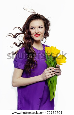 Portrait of a lovely girl with yellow tulips against white background - stock photo