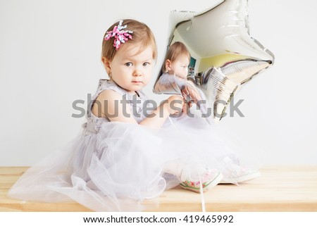 Portrait of a lovely little girl wearing elegant gray dress in front of a white background. Little princess. Little baby girl holding silver star-shaped balloon. - stock photo