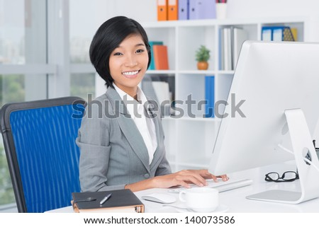 Portrait of a lovely office worker at her work place - stock photo