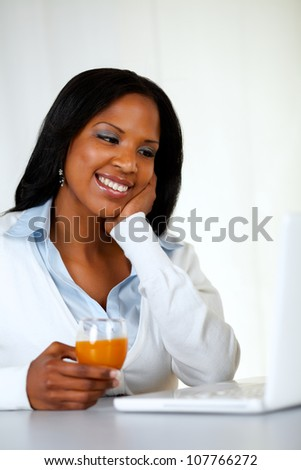 Portrait of a lovely student woman smiling and looking to laptop at soft colors composition - stock photo