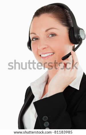 Portrait of a lovely woman in suit using headphones and posing while standing against a white background - stock photo