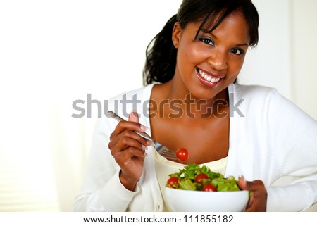 Portrait of a lovely young female enjoining fresh vegetable salad while looking and smiling at you - stock photo