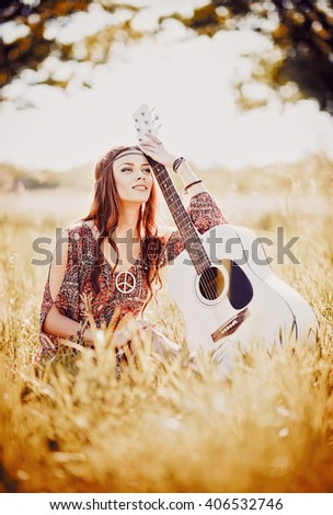 Portrait of a lovely young hippie girl with guitar. Outdoor shot - stock photo