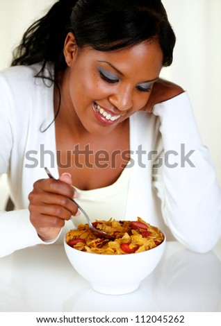 Portrait of a lovely young woman having healthy breakfast with cereals and strawberries - stock photo