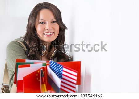 Portrait of a lovely young woman with different countries flags smiling - stock photo