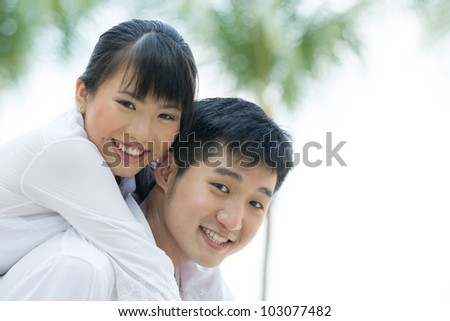 Portrait of a loving Asian couple enjoying themselves on holiday. - stock photo