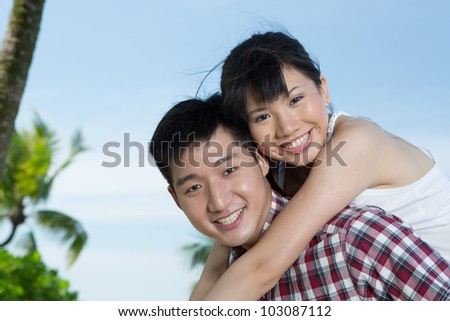 Portrait of a loving Asian man and woman enjoying themselves on holiday. - stock photo