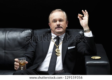 Portrait of a mafia boss relaxing with a glass of whiskey and a cigar