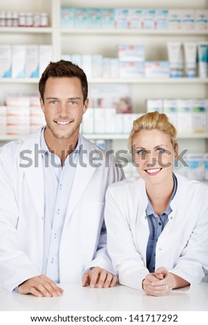 Portrait of a male and female pharmacists smiling in front of medicines at drugstore - stock photo