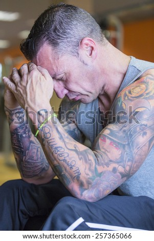 portrait of a male athlete on a pose concentrated with his hands on the forehead at the gym - focus on the man face - stock photo
