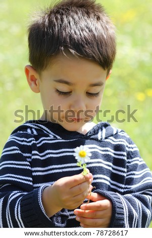 Portrait of a male child with a daisy