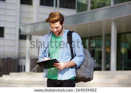 Portrait of a male college student standing outside with notepad and bag - stock photo