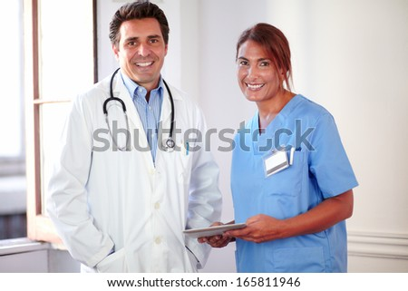 Portrait of a male doctor and female nurse on medical uniform looking at you while standing and holding a tablet pc