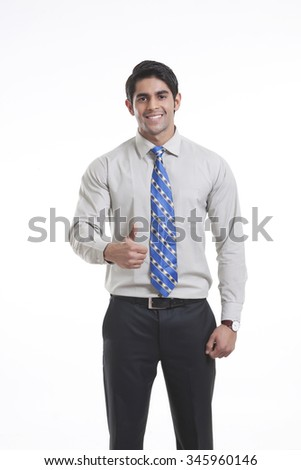 Portrait of a male executive giving thumbs up - stock photo