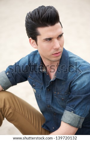Portrait of a male fashion model sitting outdoors - stock photo