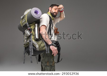 Portrait of a male fully equipped tourist with backpack and the camera on gray background. side view. tourist looking into the camera and  wiping sweat - stock photo