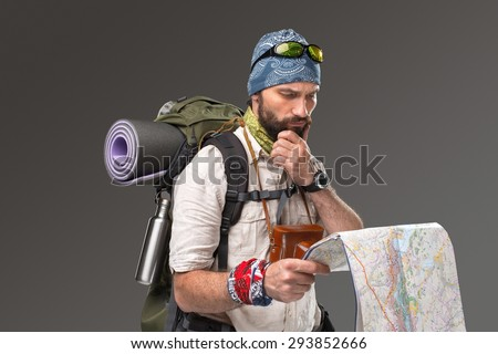 Portrait of a male fully equipped tourist with backpack and the camera on gray background. tourist looking at a map - stock photo