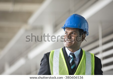 Portrait of a male Indian, industrial engineer at work. Asian engineer smiling & looking away optimistically.