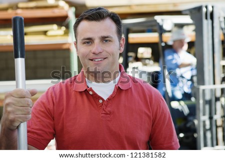 Portrait of a male industrial worker holding rod with coworker in the background