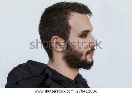 Portrait of a male model with Smokey eyes and black clothes - stock photo