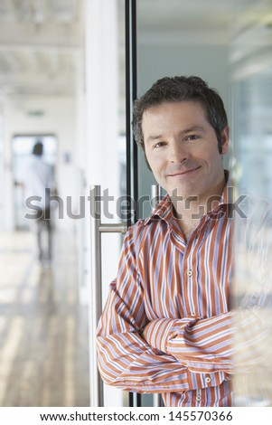 Portrait of a male office worker in striped shirt standing in doorway