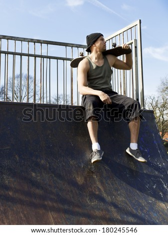 Portrait of a male skateboarder sitting on a half-pipe - stock photo