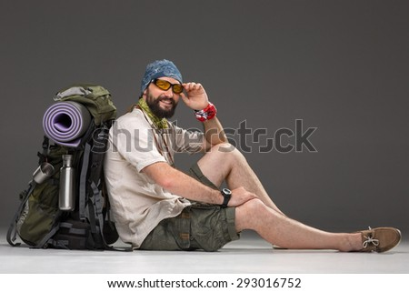 Portrait of a male smiling fully equipped tourist with backpack and the camera sitting on gray background - stock photo