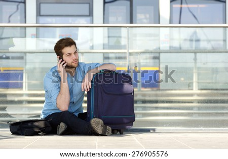 Portrait of a male traveler sitting on floor with bag, talking on mobile phone - stock photo