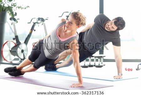 Portrait of a man and a woman doing plank exercises at the fitness center.
