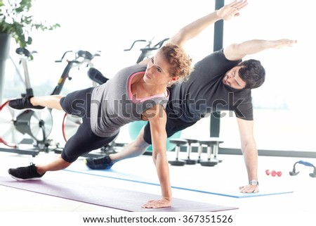 Portrait of a man and a woman doing plank exercises at the fitness center.  - stock photo