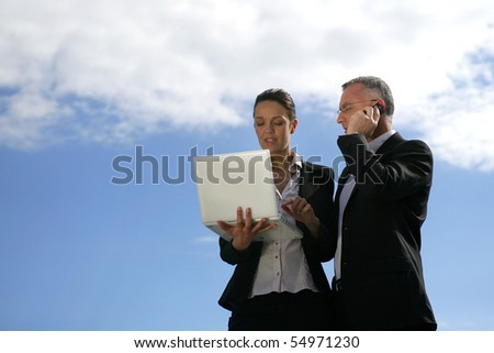 Portrait of a man and a woman with a laptop computer and a phone - stock photo