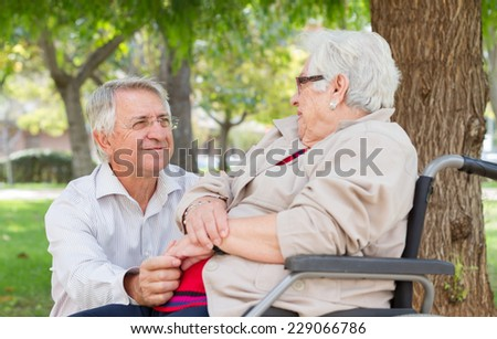 Portrait of a man and senior woman in wheel chair talking at the park - stock photo