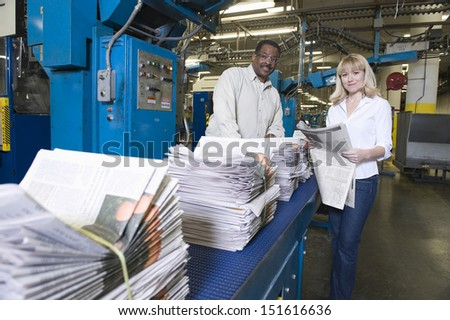 Portrait of a man and woman working in newspaper factory - stock photo