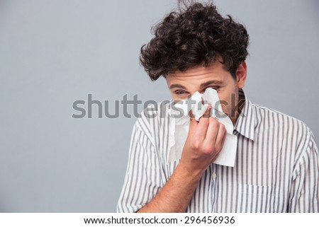 Portrait of a man blowing his nose over gray background - stock photo