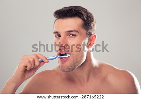 Portrait of a man brushing his teeth over gray background and looking at camera