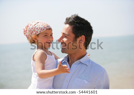 Portrait of a man carrying a little girl in his arms - stock photo