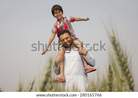 Portrait of a man carrying little boy on shoulders - stock photo