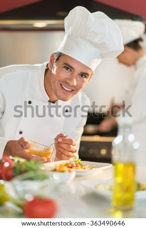 Portrait of a man chef in his forties. He is looking at camera and about to put sauce on a plateful. He is wearing white chef clothes and hat. Another woman chef is cooking in the blurred background. - stock photo