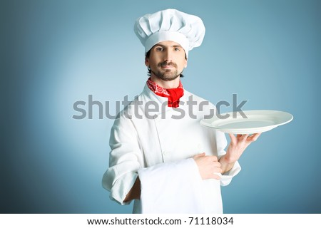 Portrait of a man cook holding a plate. Shot in a studio over grey background. - stock photo