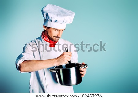 Portrait of a man cook holding a saucepan and ladle. Shot in a studio. - stock photo