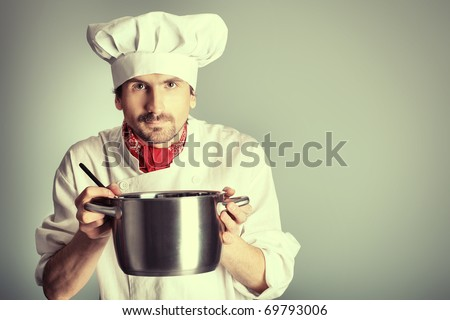 Portrait of a man cook holding a saucepan. Shot in a studio over grey background. - stock photo