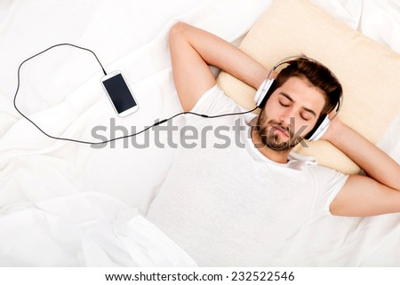 Portrait of a man from above with headphones and smartphone in bed.  - stock photo