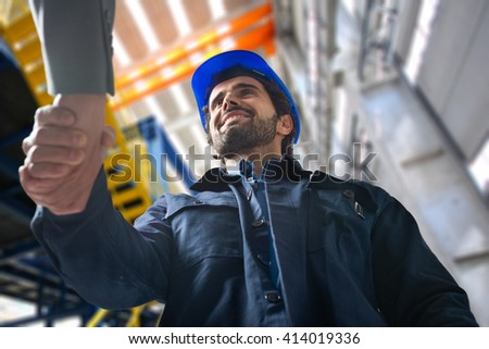 Portrait of a man giving an handshake in an industrial facility - stock photo