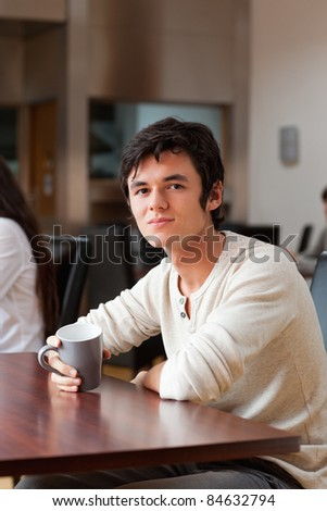 Portrait of a man having a coffee while looking at the camera - stock photo