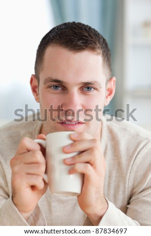 Portrait of a man having a tea in his living room - stock photo