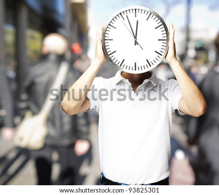 portrait of a man holding a big clock in front of his head at a crowded place - stock photo