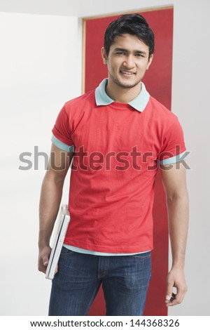Portrait of a man holding a laptop - stock photo