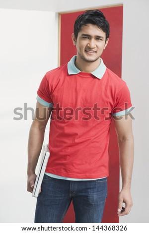 Portrait of a man holding a laptop - stock photo