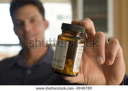 Portrait of a man holding a pill bottle - stock photo